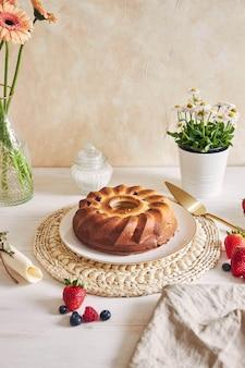 Tiro vertical de um bolo de anel com frutas em uma mesa branca com fundo branco