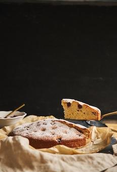 Tiro vertical de um bolo de cereja com açúcar em pó e ingredientes ao lado em um fundo preto