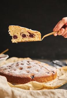 Tiro vertical de um bolo de cereja com açúcar em pó e ingredientes na lateral em preto