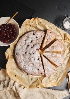 Tiro vertical de um bolo de cereja com açúcar em pó e ingredientes