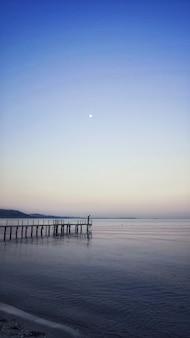 Tiro vertical de um cais, levando a uma vista deslumbrante do oceano