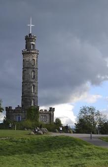 Tiro vertical de um caminho com pessoas andando perto de um campo gramado e uma torre sob um céu nublado