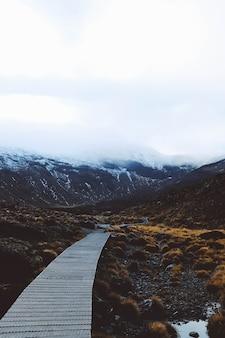 Tiro vertical de um caminho de madeira com as montanhas cobertas de neve