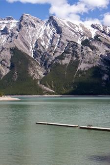 Tiro vertical de um caminho sobre o mar com montanhas arborizadas