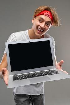 Tiro vertical de um cara alegre em uma bandana com um laptop com uma tela em branco para a frente com um sorriso largo com os dentes em um fundo cinza isolado
