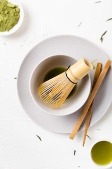 Tiro vertical de um chá matcha verde em uma mesa branca
