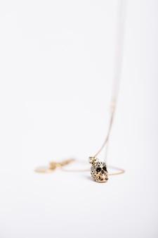 Tiro vertical de um colar com um charme de caveira no fundo branco