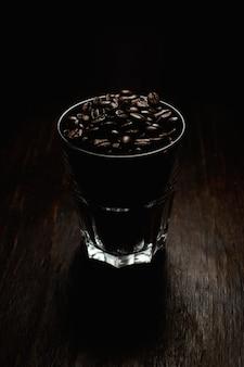 Tiro vertical de um copo de vidro cheio de grãos de café em uma superfície de madeira com um fundo preto