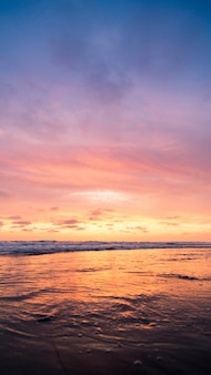 Tiro vertical de um corpo de água com o céu rosa durante o pôr do sol. perfeito para um papel de parede.