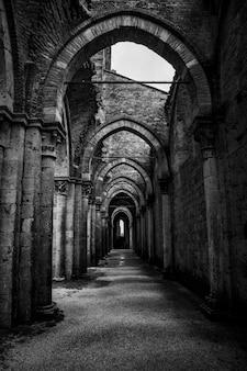 Tiro vertical de um corredor com pilares e portas em arco no abbazia di san galgano