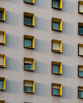 Tiro vertical de um edifício branco com molduras de janelas pretas e amarelas