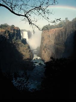 Tiro vertical de um fluxo de água no meio de falésias e uma cachoeira à distância