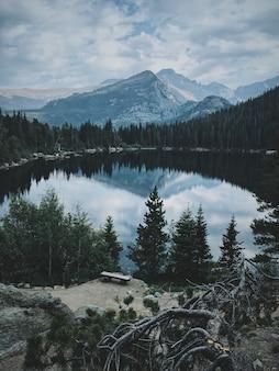 Tiro vertical de um grande lago cercado por árvores com uma bela montanha
