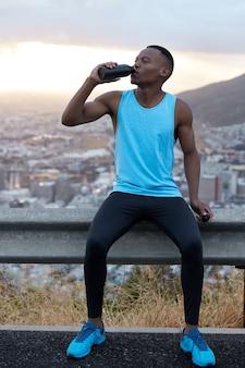 Tiro vertical de um homem afro-americano bonito em roupas esportivas bebe água após o treinamento físico, se refresca com bebida, posa sobre a colina de montanha, sente fadiga. conceito de esporte e rejuvenescimento