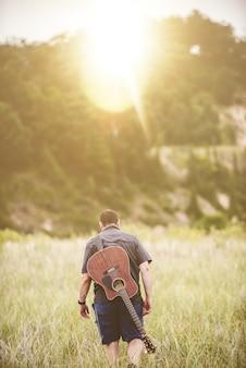 Tiro vertical de um homem andando em um campo ao lado de uma floresta com um violão nas costas
