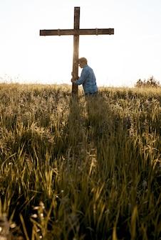 Tiro vertical de um homem com a cabeça contra uma cruz de madeira em um campo gramado