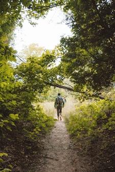 Tiro vertical de um homem com uma mochila andando em um caminho estreito no meio de árvores e plantas
