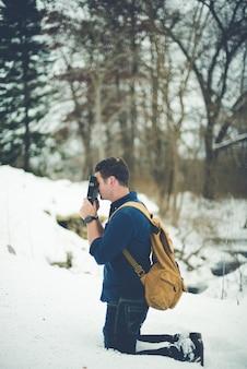 Tiro vertical de um homem de joelhos no chão nevado, mantendo a bíblia contra a cabeça rezando
