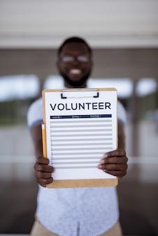 Tiro vertical de um homem segurando a folha de inscrição voluntária