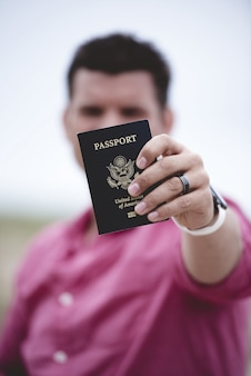 Tiro vertical de um homem segurando seu passaporte em direção à câmera com um fundo desfocado