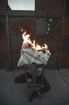 Tiro vertical de um homem sentado em uma cadeira lendo um jornal em chamas concept- fake news