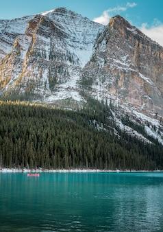 Tiro vertical de um lago turquesa sob floresta e uma montanha de neve no fundo