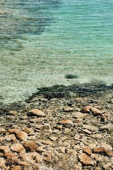 Tiro vertical de um mar de águas claras perto das rochas durante o dia