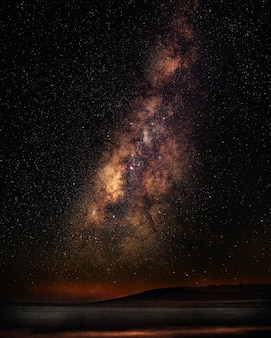 Tiro vertical de um mar sob um céu estrelado com a via láctea
