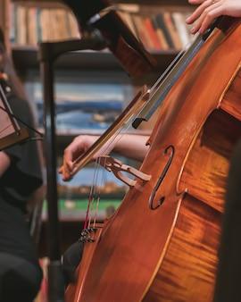 Tiro vertical de um músico tocando violino em uma orquestra