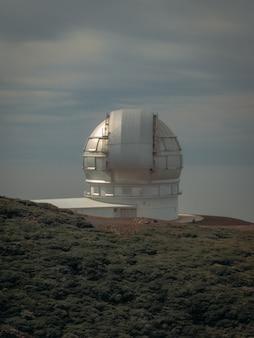 Tiro vertical de um observatório de construção em uma montanha perto de um campo gramado