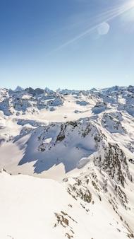 Tiro vertical de um pico de montanha cênico coberto de neve durante o dia.