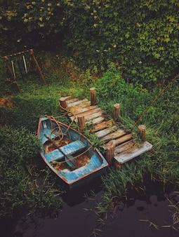 Tiro vertical de um velho barco na água perto de uma doca de madeira, rodeada por vegetação