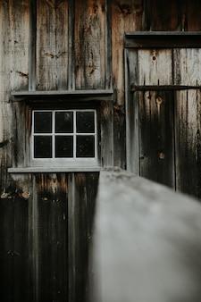 Tiro vertical de um velho galpão de madeira com uma pequena janela branca