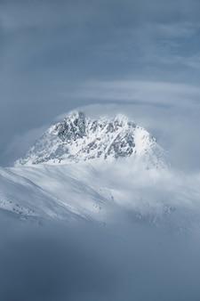 Tiro vertical de uma bela colina rochosa coberta de neve, envolvida no nevoeiro