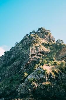 Tiro vertical de uma bela formação rochosa coberta de musgo sob o céu azul