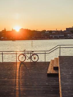 Tiro vertical de uma bicicleta estacionada na costa do mar, perto do porto durante o pôr do sol