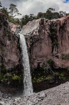 Tiro vertical de uma cachoeira no meio de falésias sob um céu nublado
