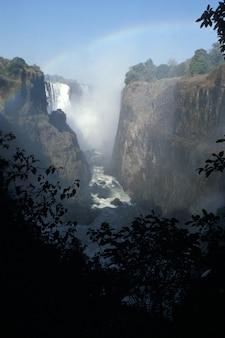 Tiro vertical de uma cachoeira que flui para baixo de colinas altas sob um céu azul com um arco-íris
