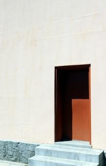 Tiro vertical de uma casa branca com uma porta marrom em um dia ensolarado