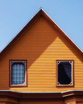 Tiro vertical de uma casa de madeira laranja sob o céu azul claro