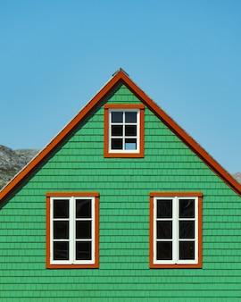Tiro vertical de uma casa verde de madeira sob o céu azul claro