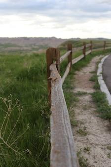 Tiro vertical de uma cerca de madeira no meio de uma estrada e um campo de grama