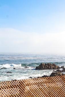 Tiro vertical de uma cerca de madeira perto de uma costa rochosa e um mar