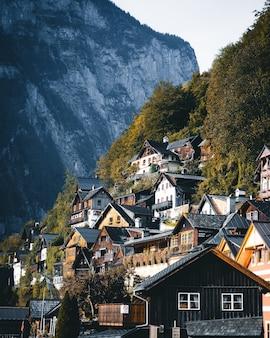 Tiro vertical de uma colina com árvores e casas em cascata. lindos telhados em uma ilha sob o sol