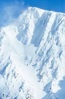 Tiro vertical de uma cordilheira alta coberta de neve sob o céu azul claro