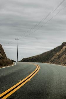 Tiro vertical de uma estrada frente e verso, rodeada por colinas com o céu cinzento nublado no