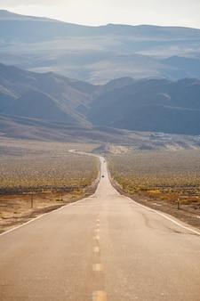 Tiro vertical de uma estrada que atravessa as magníficas montanhas capturadas na califórnia