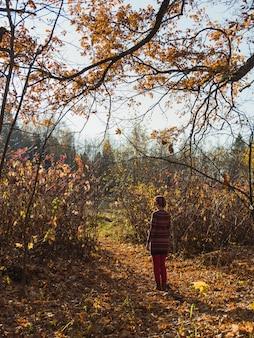 Tiro vertical de uma fêmea em uma boina em pé no jardim com folhas de outono caídas