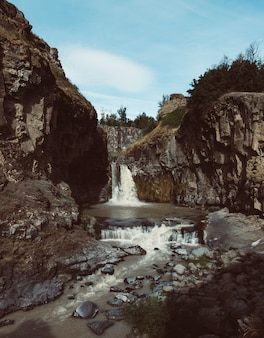 Tiro vertical de uma forte cachoeira que flui no rio entre rochas enormes