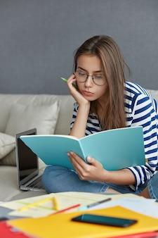 Tiro vertical de uma jovem empresária europeia de aparência agradável examina alguns papaerwork, trabalha em casa no sofá.